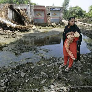 A Pakistani woman carries her baby in front of a damaged house in Punjab Province, Pakistan (AP)