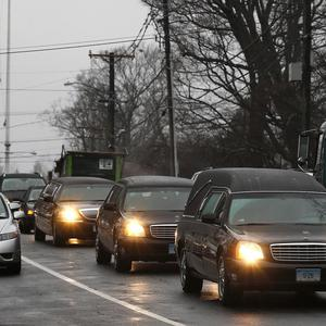 A hearse and family limousines pass a flag at half-mast as the funeral procession for shooting victim Jack Pinto heads through Newtown (AP)