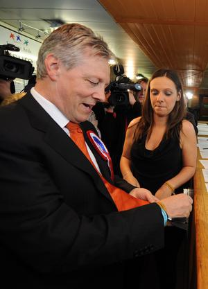 First Minister and DUP leader Peter Robinson, pictured with daughter Rebekah, puts on an id braclet after he was asked for id before being allowed to enter the count at Newtownards Leisure Centre in the Northern Ireland Assembly elections