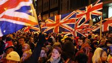 Loyalist protestors carrying Union flags outside City Hall in Belfast where councillors were debating whether or not to keep it flying at the building