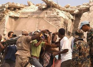 People carry an injured person after an earthquake in Port-au-Prince, Haiti, Tuesday, Jan. 12, 2010