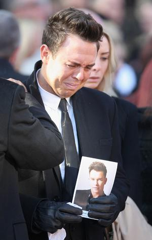 A mourner crys at the funeral of Boyzone singer Stephen Gately at St Laurence O'Toole Church in Dublin