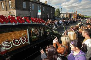 Fans watch the coffin of Stephen Gately pass by outside St Laurence O'Toole Church in Dublin