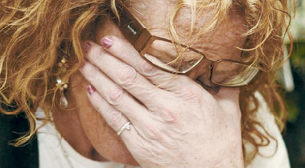 Mrs Ann Henry, from Portglenone, breaks down yesterday after seeing the damage caused to her home