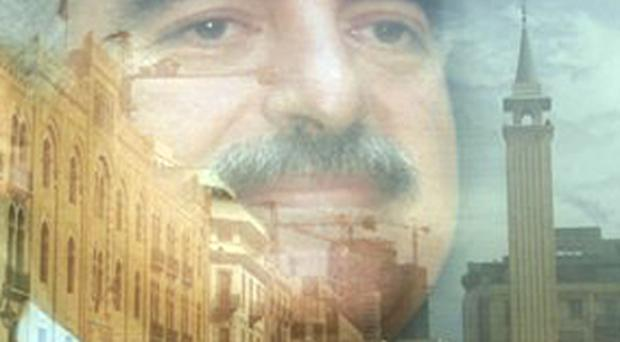 The buildings of Beirut's downtown are seen reflected on a portarit of the slain former Lebanese Prime Minister Rafik Hariri, which is set on the street in preparation to the third anniversary of his assassination, in downtown of Beirut, Lebanon, Tuesday Feb. 12, 2008. Pro-government and anti-Syrian factions are mobilizing their supporters for a massive rally to mark Thursday's third anniversary of the assassination of former Prime Minister Rafik Hariri in a show of force against the Syrian-backed opposition led by Hezbollah.