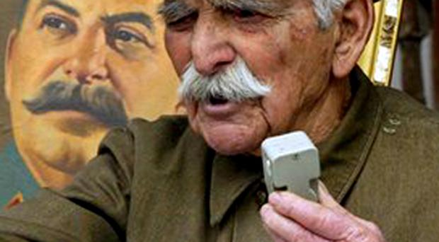 Georgian Georgy Buziashvili speaks in front of a portrait of Soviet dictator Joseph Stalin during a rally marking the 54th anniversary of his death in his hometown of Gori, some 80 km (50 miles) west of Tbilisi, Georgia, Monday, March 5, 2007