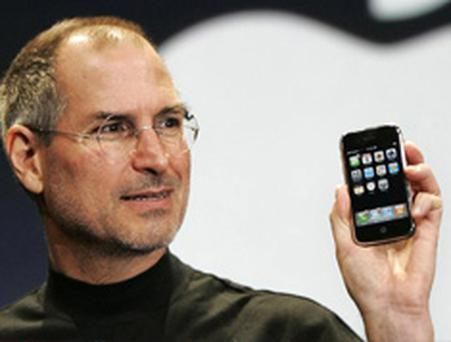 Apple chief executive Steve Jobs holds up the 'revolutionary' iPhone