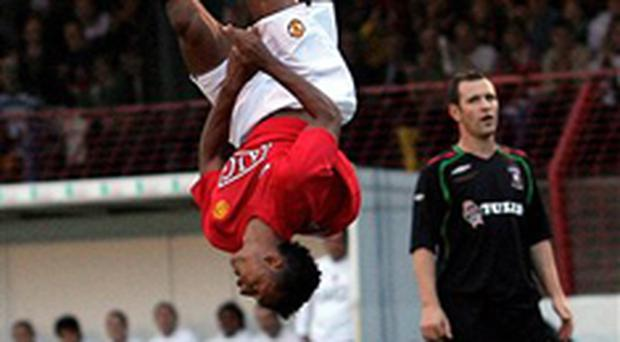 Rory Hamill looks on as Manchester United's Nani celebrates in style after scoring against Glentoran at the Oval last night