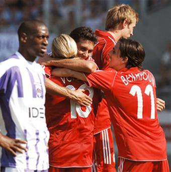 Andriy Voronin of Liverpool is congratulated by an teammates as Mohamed Fofana of Toulouse FC and referee Kyros Vassaras look on