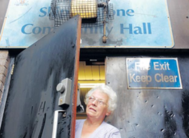 Florrie Burns at the fire-damaged door and entrance area at Skipperstone Road Community Hall in Bangor
