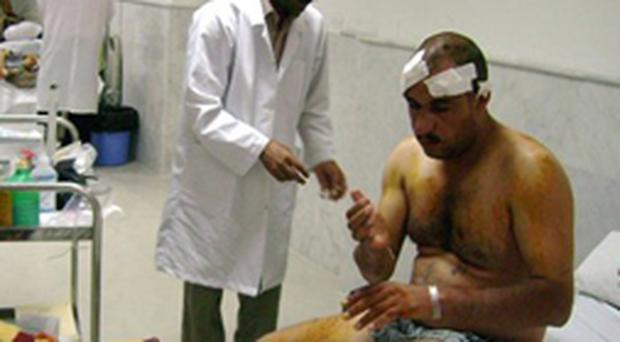 A doctor treats an injured man at a hospital in Dahuk, 430 kilometers (260 miles) northwest of Baghdad, Iraq on Wednesday, Aug. 15, 2007