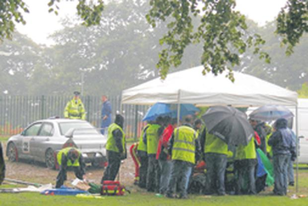 Rescue workers attend the injured after a rally car crashed into spectators at Lurgan Park, Co Armagh