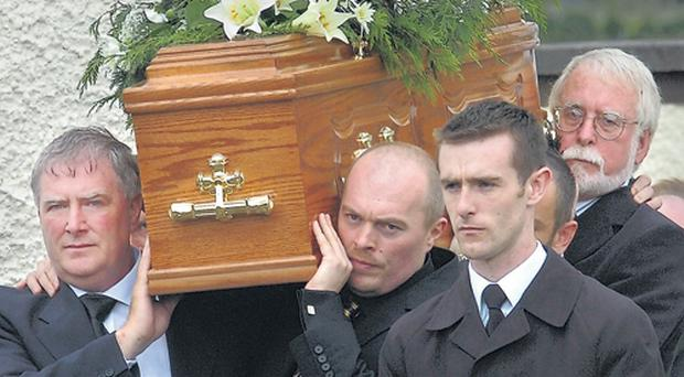 Caroline Kewley's brother Mark Clarke (left) helps family and friends carry the coffin at the shot police officer's funeral in Newry yesterday