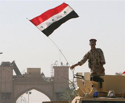 An Iraqi soldier waves his national flag from top of an armored vehicle in front of the gates to the Basra Palace. Iraqi soldiers hoisted the nation's flag over the Basra palace compound on Monday after British troops began withdrawing from their last garrison in the city