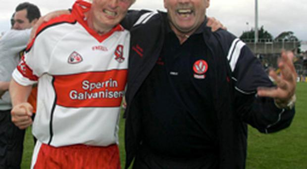 Derry's Ciaran McFeely and his father Noel celebrate at the final whistle after their win over Laois