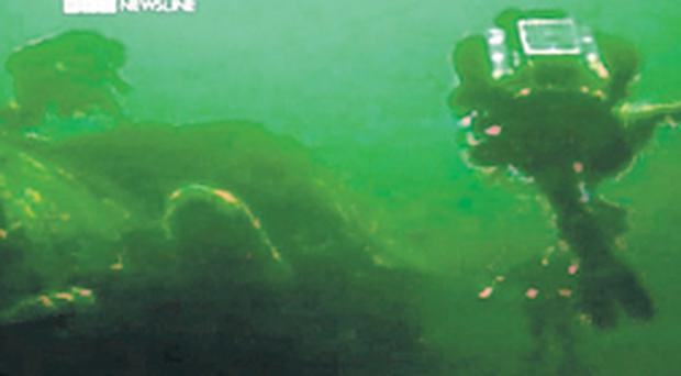 Divers swim over the wreck of a sunken U-boat
