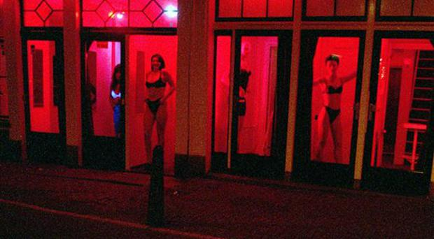 Prostitutes stand behind red-lit windows, waiting for customers in Amsterdam's Red Light district