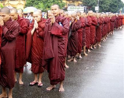 Buddhist monks march and pray during a peaceful protest against the military government on the street of Yangon