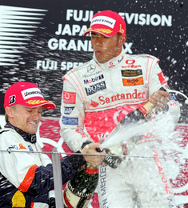 Lewis Hamilton, right, splashes a bottle of champagne with second placer Renault's Finnish Heikki Kovalainen on the podium after winning the Formula One Japanese Grand Prix at the Fuji Speedway circuit