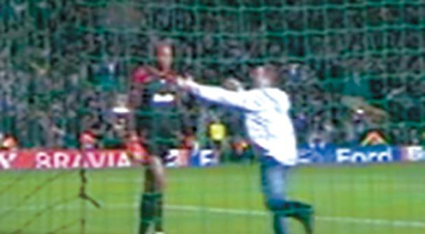 A fan appears to assault Milan keeper Dida during last night's Champions League game