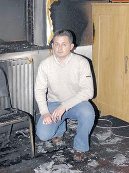 Craigavon councillor Mark Russell inspects the fire damage at Tamnificarbet Orange Hall outside Portadown
