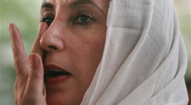 Benazir Bhutto wipes her face whilst speaking to the media at her residence in Karachi