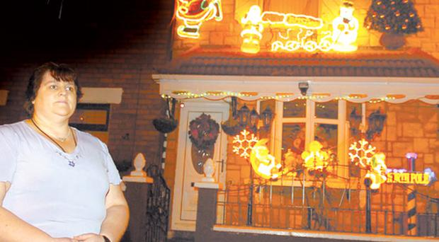 Anna Marie McArdle outside her west Belfast house bedecked in festive lights yesterday
