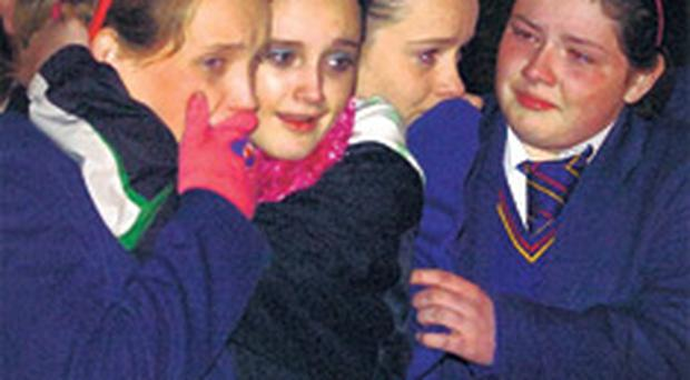 School children weep as the bodies of the McElhill family leave the burnt-out home last night