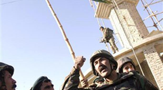 General Mahayadin, bottom right, from the Afghan National Army (ANA) reacts as Afghanistan's national flag is raised in the center of Musa-Qala