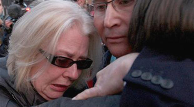 Victor Barker, centre, who lost his son James in the 1998 Omagh bomb is comforted by wife Donna Maria and son Oliver after leaving Lagonside Courts