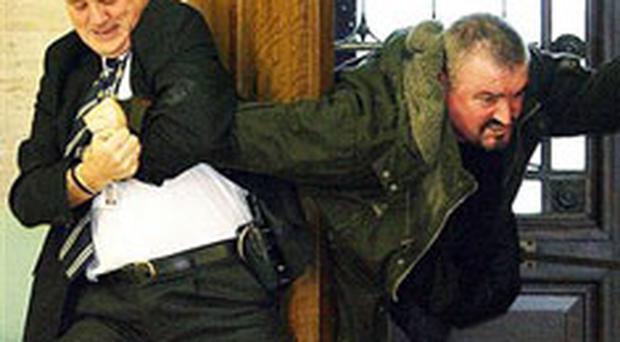 Security guard restrains Michael Stone at the Stormont door