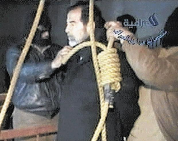 Guards wearing balaclavas place the noose around Saddam's neck