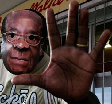 A person wearing a mask of Zimbabwean President Robert Mugabe chants opposition MDC (Movement For Democratic Change) slogans