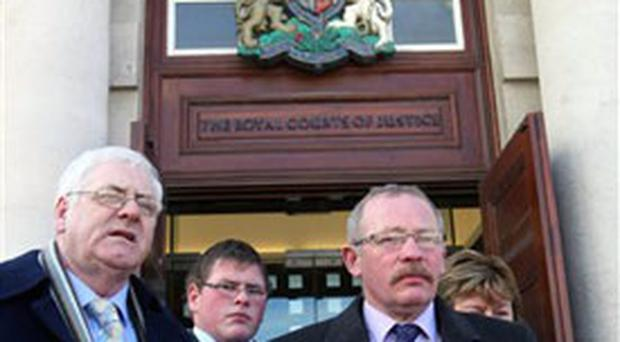 Michael Gallagher, left, spokesperson for the Omagh families, and Godfrey Wilson, right, speak to the media at the High Court in Belfast