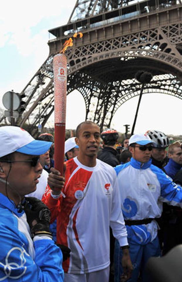 French athlete Stephane Diagana, surrouned by Chinese officials, holds the Olympic torch in front of the Eiffel Tower