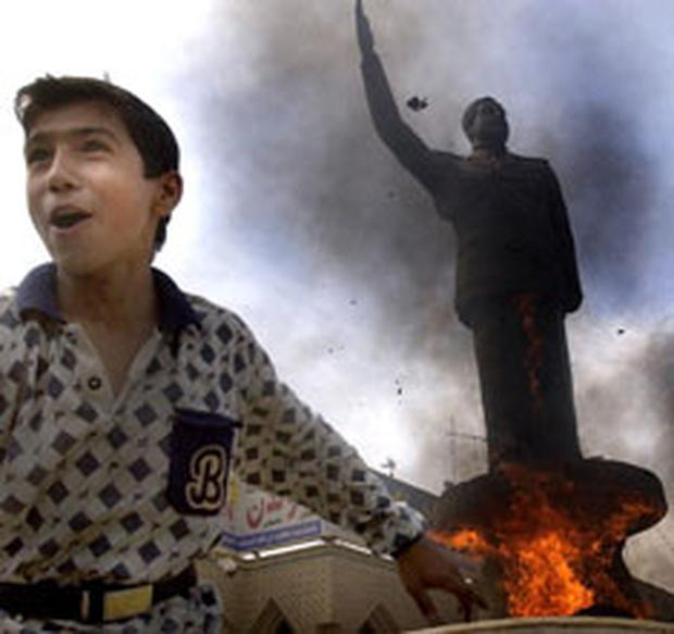 An Iraqi boy cheers as a statue of ousted Iraqi President Saddam Hussein is set ablaze in 2003