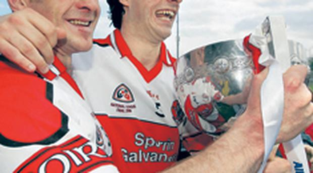 Derry captain Kevin McCloy and Liam Hinphey proudly display the Division 1 League trophy after conquering Kerry