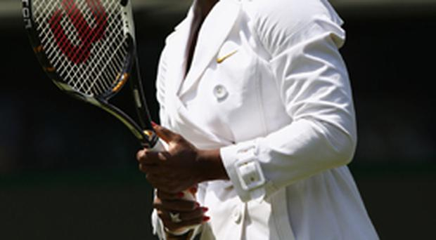 Serena Williams wears a white raincoat as she warms up for her opening 7-5, 6-3 victory over Estonia's Kaia Kanepi on Court One yesterday