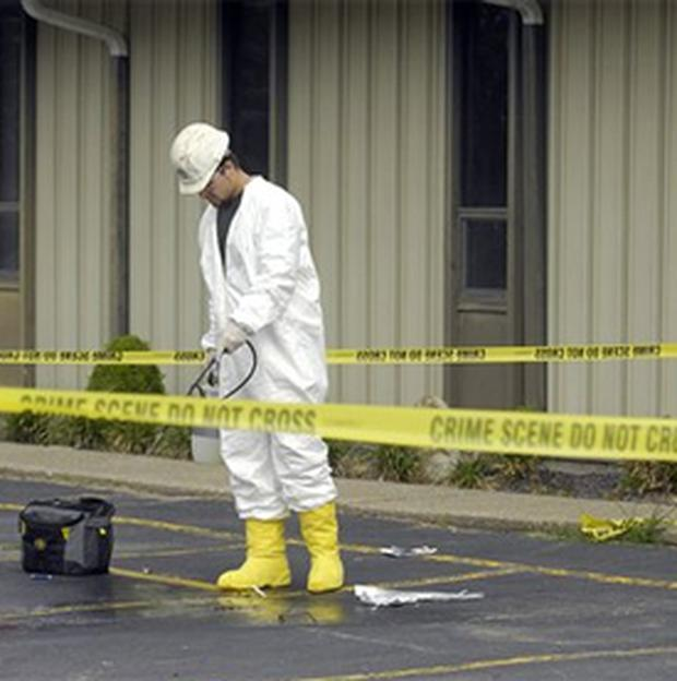 A worker cleans up an area surrounded by crime scene tape. AP