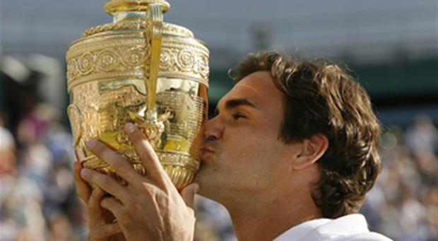 Switzerland's Roger Federer kisses the trophy after defeating Rafael Nadal to win his fifth consecutive Men's Singles Championship on the Centre Court at Wimbledon