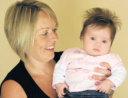 Baby Freya Spencer, who has the hair of a two-year-old, despite being aged only 12 weeks, in the arms of proud mum Kirsty