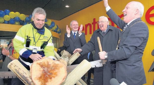 Belfast Lord Mayor Jim Rodgers, saws a log to offically open the first IKEA store in Ireland with First and Deputy First Ministers Ian Paisley (right) and Martin McGuinness.