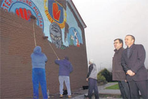 The first of three murals which was painted over as part of phrase one of 'Re-imaging Kilcooley Toward a Shared Future'. Robert Mahaffy, district manager of the Housing Executive, and Mark Gordon who helped facilitate the project, look on at the start of the £10,000 facelift