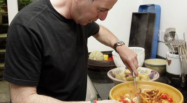 Loyd Grossman cooks tomato and basil sauce with mozzarella and aubergine, alongside Italian chef Anthony Warner, at his home in London.