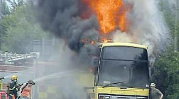 The bus in flames on the hard shoulder of the southbound lane of the M50