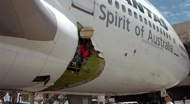 Qantas pilot Capt. John Francis Bartels look at the right wing damaged fuselage of Qantas Airways Boeing 747-400 after it made an emergency landing