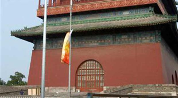 A Chinese man cycles past the Drum Tower in Beijing, China, Saturday, Aug. 9, 2008. Beijing authorities say a Chinese man attacked two American tourists on the opening day of the Olympic Games, killing one of them before committing suicide.