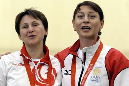 Russia's Natalia Paderina, left, and Georgia's Nino Salukvadze embrace during the medal ceremony after the women's 10 meter air pistol final at the Beijing 2008 Olympics in Beijing, Sunday, Aug. 10, 2008. Paderina won the silver medal and Salukvadze won bronze.