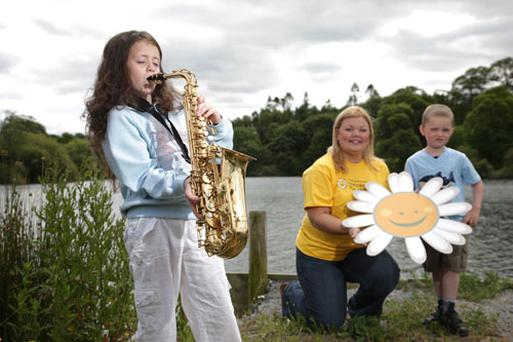 Cara McKeating, 9, tunes up for the Lazy Daisy Fun Day at Delamont Country Park. Also pictured are Joanne Steele and Michael McKeating, 4