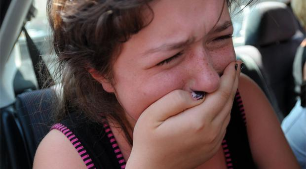 A girls weeps in the back of a car as people flee on foot and in cars from the town of Gori, on August 13, 2008, in Georgia